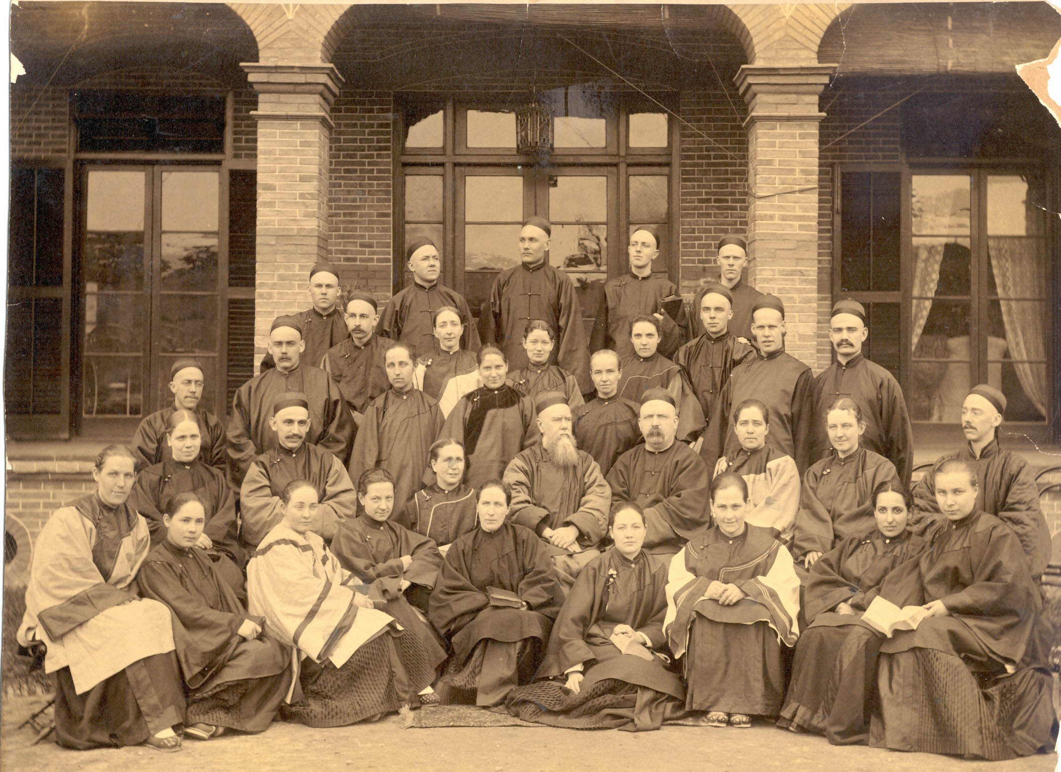 China Inland Mission missionaries in Chinese dress (1891). Hudson Taylor is seated in the middle of the second row with full gray beard.