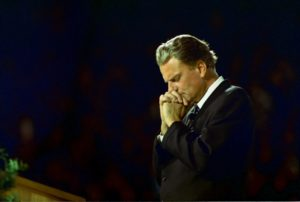 Billy Graham praying during a public invitation